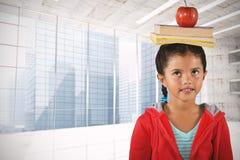 Sammansatt bild av flickan som balanserar böcker och äpplet på huvudet Arkivbild