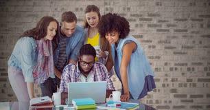 Sammansatt bild av folk runt om bärbara datorn mot tegelstenväggen Arkivfoton