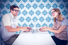 Sammansatt bild av geeky hipsterpar genom att använda bärbara datorn Royaltyfria Foton
