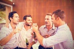 Sammansatt bild av gruppen av unga män som har drinkar Royaltyfri Bild