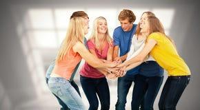 Sammansatt bild av gruppen av vänner omkring som ska hurras med deras staplade händer royaltyfri fotografi
