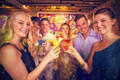 Sammansatt bild av gruppen av vänner som rostar exponeringsglas av coctailen i stång royaltyfri fotografi