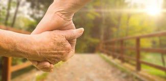 Sammansatt bild av händer för åldringparinnehav royaltyfri bild