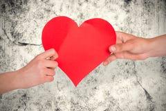 Sammansatt bild av händer som rymmer röd hjärta Royaltyfri Foto