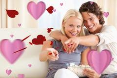 Sammansatt bild av hållande ögonen på tv för gulliga par, medan äta popcorn Arkivbilder