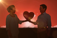 Sammansatt bild av hållande hjärta för äldre asiatiska par Royaltyfria Foton