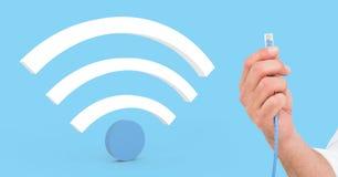 Sammansatt bild av hållande kabel för hand och det digitala Wifi symbolet arkivbild