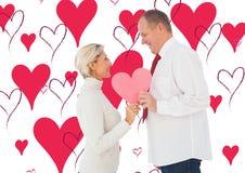 Sammansatt bild av hållande rosa hjärtaform för äldre tillgivna par Royaltyfria Foton