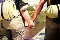 Sammansatt bild av haken som fotvandrar stående innehavhänder för par på vägen Royaltyfri Bild