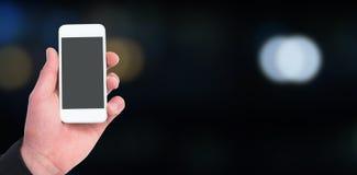 Sammansatt bild av handen av smarta telefoner 3d för affärsmaninnehav Royaltyfri Bild