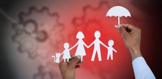 Sammansatt bild av handen som rymmer ett paraply och en familj i papper Royaltyfria Foton