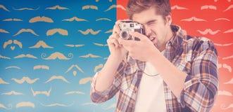 Sammansatt bild av hipsteren som fotograferar mot träväggen Royaltyfri Foto