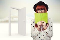 Sammansatt bild av hipsterkvinnan bak en grön bok Arkivbild