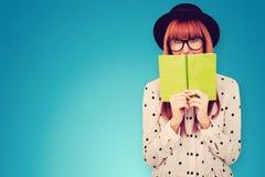 Sammansatt bild av hipsterkvinnan bak en grön bok Royaltyfri Fotografi