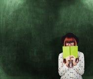 Sammansatt bild av hipsterkvinnan bak en grön bok Royaltyfri Foto