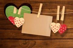 Sammansatt bild av hjärtor som hänger på linje med kortet Royaltyfria Bilder