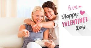 Sammansatt bild av hållande ögonen på tv för gulliga par, medan äta popcorn Arkivfoton