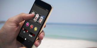 Sammansatt bild av kasinoenarmade banditen på mobil skärm fotografering för bildbyråer