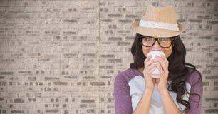 Sammansatt bild av kvinnan med kaffe mot tegelstenväggen Arkivbild