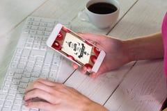 Sammansatt bild av kvinnan som använder smartphonen på arbete Arkivbild
