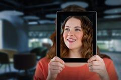 Sammansatt bild av kvinnan som rymmer den digitala minnestavlan främst av hennes framsida Royaltyfria Bilder