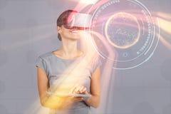 Sammansatt bild av kvinnan som rymmer den digitala minnestavlan och använder virtuell verklighethörlurar med mikrofon Arkivfoton