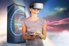 Sammansatt bild av kvinnan som rymmer den digitala minnestavlan och använder virtuell verklighethörlurar med mikrofon 3d Royaltyfri Fotografi