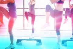 Sammansatt bild av kvinnor som lyfter deras ben, medan göra aerobics Arkivfoto
