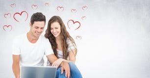 Sammansatt bild av lyckliga par genom att använda bärbara datorn Royaltyfri Foto