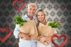 Sammansatt bild av lyckliga par som bär pappers- livsmedelsbutikpåsar Fotografering för Bildbyråer