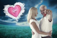 Sammansatt bild av lyckliga par som visar deras tangent för nytt hus Fotografering för Bildbyråer