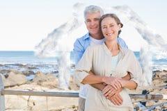 Sammansatt bild av lyckliga tillfälliga par som kramar vid kusten Arkivfoton
