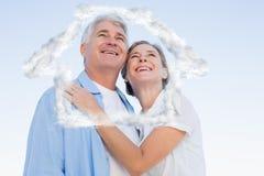 Sammansatt bild av lyckliga tillfälliga par som omfamnar under blå himmel Arkivfoto