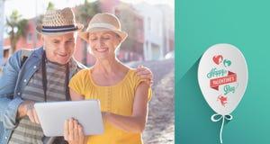 Sammansatt bild av lyckliga turist- par genom att använda minnestavlaPC i staden Arkivbild