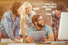 Sammansatt bild av lyckligt affärsfolk som använder den digitala minnestavlan på datorskrivbordet Royaltyfri Foto