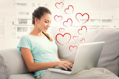 Sammansatt bild av lyckligt kvinnasammanträde på soffan genom att använda hennes bärbar dator arkivbild