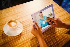 Sammansatt bild av mannen med den hållande kaffekoppen för tidning på tabellen Royaltyfria Foton
