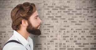 Sammansatt bild av mannen med skägget mot tegelstenväggen Royaltyfri Fotografi