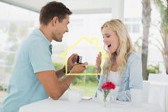 Sammansatt bild av mannen som föreslår förbindelse till hans chockade blonda flickvän Royaltyfria Bilder