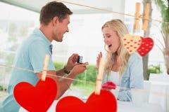 Sammansatt bild av mannen som föreslår förbindelse till hans chockade blonda flickvän Fotografering för Bildbyråer