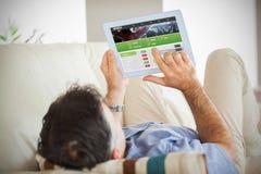Sammansatt bild av mannen som lägger på soffan genom att använda en minnestavlaPC royaltyfri fotografi