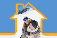 Sammansatt bild av mannen som piggybacking den gladlynta kvinnan mot den snöade kullen Arkivfoton