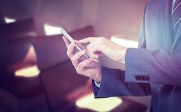 Sammansatt bild av midsectionen av affärsmannen som använder mobiltelefonen Royaltyfri Bild