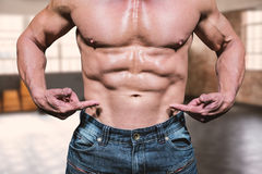 Sammansatt bild av midsectionen av den shirtless mannen som pekar på abs Arkivbild