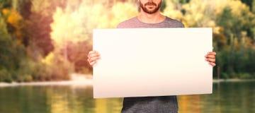 Sammansatt bild av midsectionen av hållande papp för ung man fotografering för bildbyråer