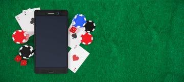 Sammansatt bild av mobiltelefonen med att spela kort och bunten av kasinotecken Royaltyfri Fotografi