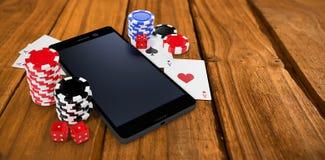 Sammansatt bild av mobiltelefonen med att spela kort och kasinotecken Arkivfoto