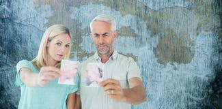 Sammansatt bild av olyckliga par som rymmer två halvor av det sönderrivna fotografiet Royaltyfria Bilder