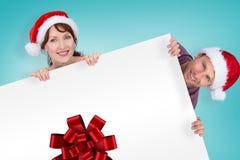 Sammansatt bild av par båda bärande santa hattar Royaltyfri Fotografi