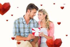 Sammansatt bild av par med gåvan Royaltyfri Foto